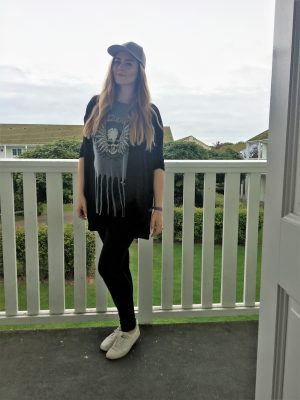 me posing outside the flat with a grey cap, grey skull top, black jeans, black cardigan and white trainers