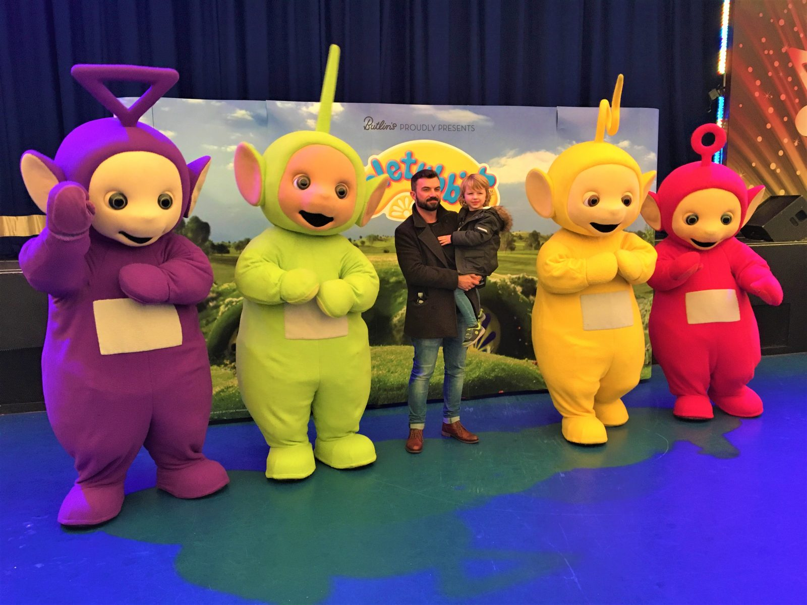my husband and son posing with the teletubbies